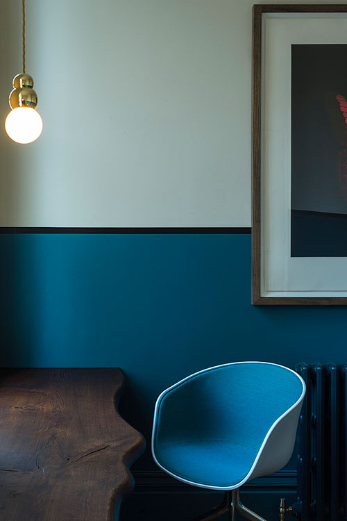 Divided by colour. An office designed to be a clear working space with character. A Victorian room, modernised with the use of colour. Artwork and lighting alongside vintage chairs, and a slice of oak as a desk.
